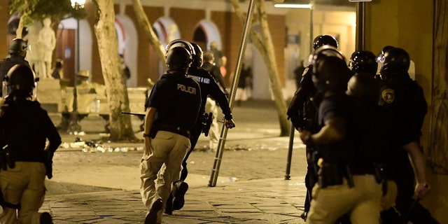 Riot control units patrol the street during clashes in San Juan, Puerto Rico, on Monday.