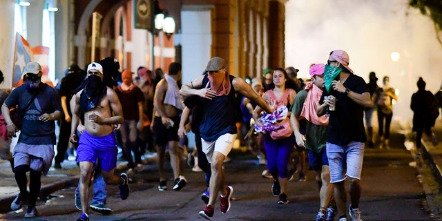 Demonstrators affected by tear gas thrown by the police run during clashes in San Juan on Monday.