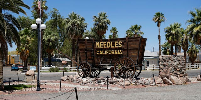 A sign adorns a historic wagon along old Route 66 in Needles, California. (Associated Press)