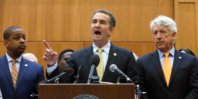 In this June 4, 2019, file photo, Virginia Gov. Ralph Northam, center, makes remarks during a news conference dealing with gun violence while Lt, Gov. Justin Fairfax, left, and Attorney General Mark Herring, right, look on inside the Patrick Henry Building in Richmond, Va. (Bob Brown/Richmond Times-Dispatch via AP, File)