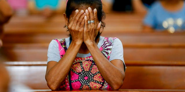 In this Mach 17, 2019, file photo, a relative of a victim in President Rodrigo Duterte's so-called war on drugs reacts during a church service in Manila, Philippines. On Thursday, July 4, 2019, the Commission on Human Rights has condemned the killing of a three-year-old girl in a crossfire in a Philippine police raid in which her father, a drug suspect, was gunned down along with another civilian and a police officer.