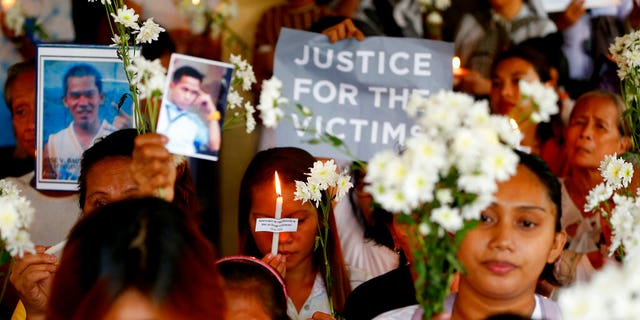 In this March 17, 2019, file photo, relatives of victims in President Rodrigo Duterte's so-called war on drugs hold a memorial for their loved ones at a church in Manila, Philippines.