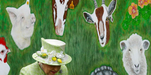 Britain's Queen Elizabeth II walks by an animal mural, during a visit to Gorgie City Farm in Edinburgh, Scotland.