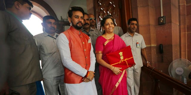 Indian Finance Minister Nirmala Sitharaman, core right, and youth Finance Minister Anurag Thakur, center, stands for a media during a council residence before phenomenon a annual sovereign bill in New Delhi, India, Friday, Jul 5.