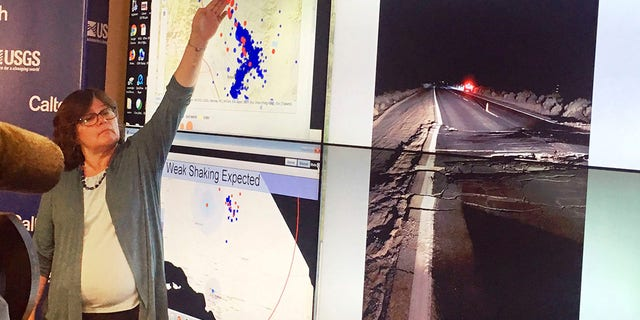 Lucy Jones, a seismologist at the California Institute of Technology and a former science adviser at the U.S. Geological Survey, points to a display of earthquakes during a news conference at CalTech in Pasadena, Calif., Friday evening, July 5, 2019. At right is a USGS photo of broken pavement on state route 178 near Trona, Calif. (Associated Press)