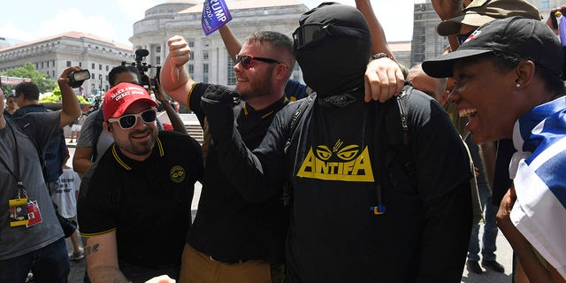 People attending a Demand Free Speech convene in Washington, Saturday, Jul 6, 2019, accumulate around an hostile protester for a photo. The convene was orderly to criticism opposite a viewed censorship of regressive views. (Associated Press)