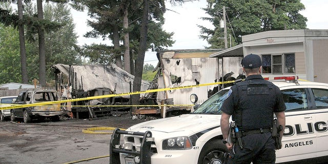Port Angeles police Officer T.J. Mueller looks over the scene of a fire that destroyed two mobile homes and left several dead early Saturday, July 6, 2019. (Associated Press)