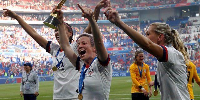 United States' Megan Rapinoe, center, with Alex Morgan, left, and Allie Long, celebrate with the trophy after winning the Women's World Cup final soccer match between the US and The Netherlands at the Stade de Lyon in Decines, outside Lyon, France, Sunday, July 7, 2019. (AP Photo/Claude Paris)