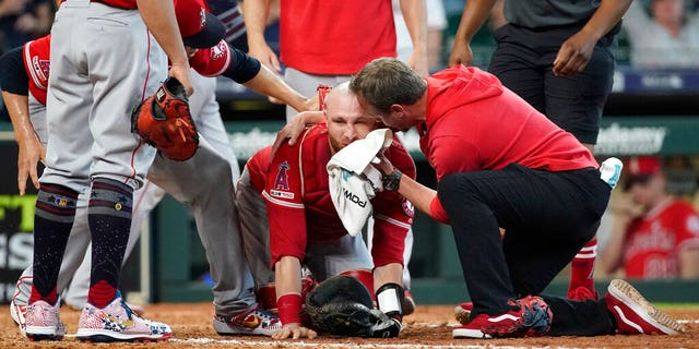 Los Angeles Angels' Jonathan Lucroy, center, is helped by medical organisation after colliding with Houston Astros' Jake Marisnick.