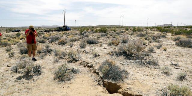 A visitor takes a photo of a crack on the ground following recent earthquakes Sunday, July 7, 2019, outside of Ridgecrest, Calif.