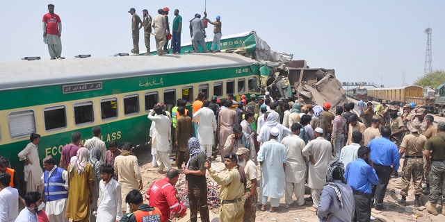 Pakistani officials and volunteers work at a train crash site in Rahim Yar Khan, Pakistan, Thursday, July 11, 2019. A passenger train rammed into a freight train in southern Pakistan on Thursday, killing many people and injuring others, an official said. (AP Photo/Waleed Saddique)