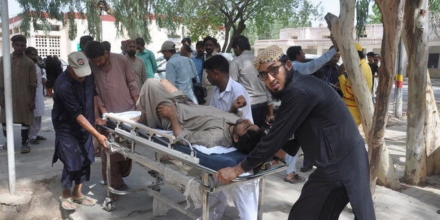 People rush an injured passenger to a hospital in Rahim Yar Khan, Pakistan, Thursday, July 11, 2019. A passenger train rammed into a freight train in southern Pakistan on Thursday, killing many people and injuring others, an official said. (AP Photo/Waleed Saddique)
