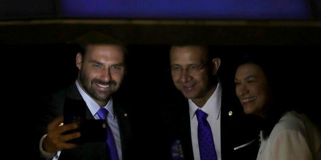 "In this Friday, Feb. 1, 2019 file photo, lawmaker Eduardo Bolsonaro, son of Brazil's President Jair Bolsonaro, left, takes a ""selfie"" during a swearing-in ceremony, at the National Assembly in Brasilia, Brazil."