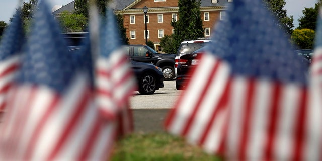 In this Saturday, June 1, 2019, file photo, American flags that are part of a makeshift memorial stand at the edge of a police cordon in front of a municipal building that was the scene of a shooting in Virginia Beach, Va. (AP Photo/Patrick Semansky, File)