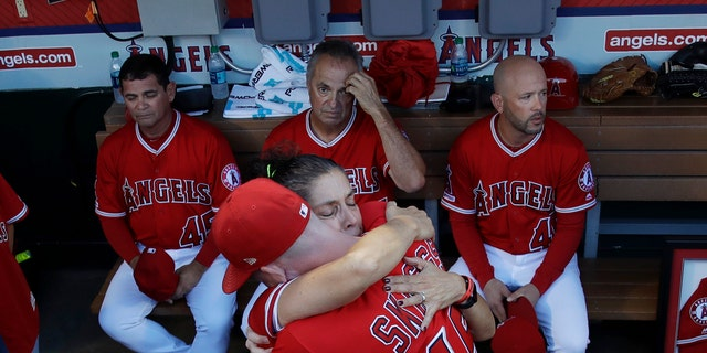 Debbie Hetman, core left, mom of a late pitcher Tyler Skaggs, hugs Angels outfielder Andrew Heaney before a initial home diversion after Skagg's death. (AP Photo/Marcio Jose Sanchez)