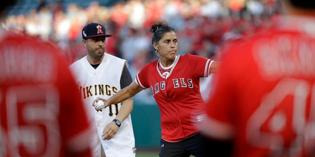 The late Los Angeles Angels pitcher Tyler Skaggs' mother, Debbie Hetman, center in red, throws the game's ceremonial first pitch, at a baseball game between the Angels and the Seattle Mariners on Friday, July 12, 2019, in Anaheim, Calif. (Associated Press)