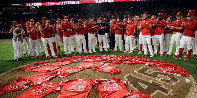 Members of the Los Angeles Angels place their jerseys with No. 45 in honor of pitcher Tyler Skaggs on the mound after a combined no-hitter against the Seattle Mariners in the first game after Skagg's death.