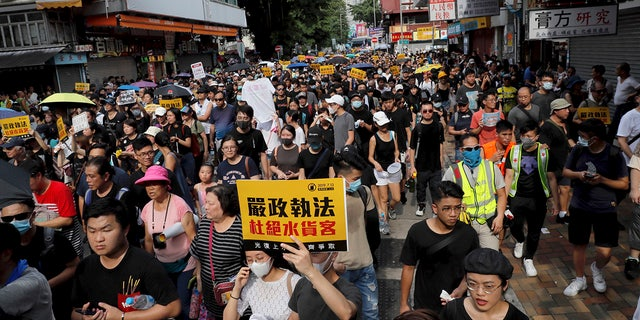 """Protesters hold up words that read: """"Strict enforcing of law against smugglers of grey goods"""" in Hong Kong Saturday, July 13, 2019. Several thousand people are marching in Hong Kong against traders from mainland China in what is fast becoming a summer of unrest in the semi-autonomous Chinese territory. (AP Photo/Kin Cheung)"""
