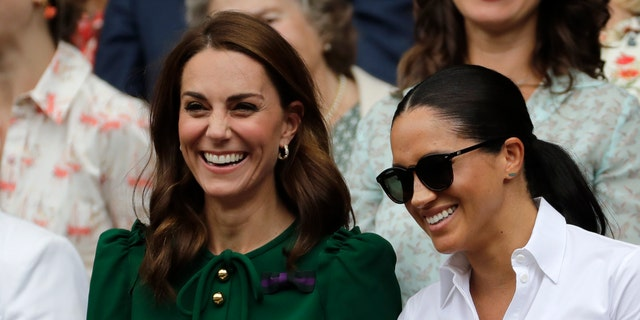 Kate, Duchess of Cambridge and Meghan, Duchess of Sussex, right, stand together during the women's singles final match on day twelve of the Wimbledon Tennis Championships in London, on July 13, 2019. (AP Photo/Ben Curtis)