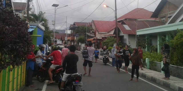 Residents leave their homes to find higher grounds following an earthquake in Ternate, North Maluku, Indonesia on Sunday. (AP Photo)