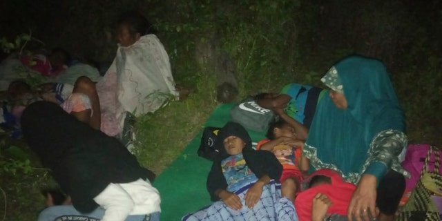 Residents sleep on the ground after leaving their homes to find higher grounds following an earthquake in Gane Utara, North Maluku, Indonesia on Sunday. (AP Photo)