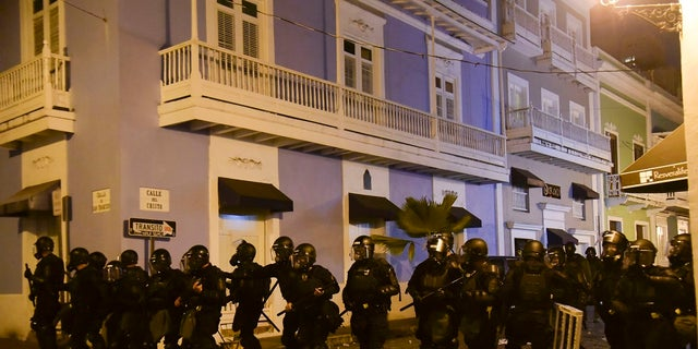 Police units protect the area near the executive mansion from protesters demanding the resignation of  Puerto Rico's governor. (AP Photo/Carlos Giusti)