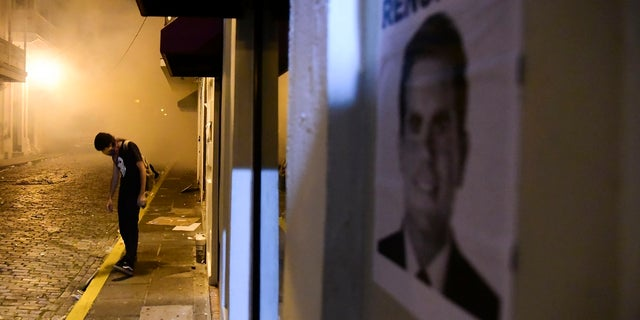 A protester stands near a poster calling for the resignation of Gov. Ricardo Rossello, in San Juan, Puerto Rico, Monday. (AP Photo/Carlos Giusti)