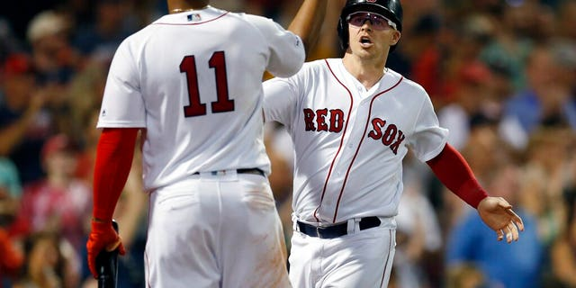 Boston Red Sox's Brock Holt celebrates with Rafael Devers (11) after scoring on a two-run single by Mookie Betts during the fifth inning of a baseball game against the Toronto Blue Jays in Boston, Tuesday, July 16, 2019.