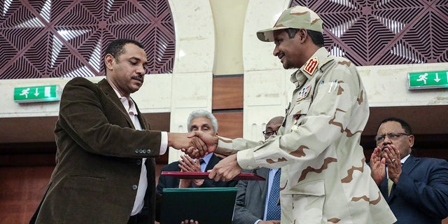 Gen. Mohammed Hamdan Dagalo, right, and Sudan's pro-democracy movement leader Ahmad al-Rabiah shake hands after signing a power-sharing document in Khartoum, Sudan, Wednesday, July 17, 2019.