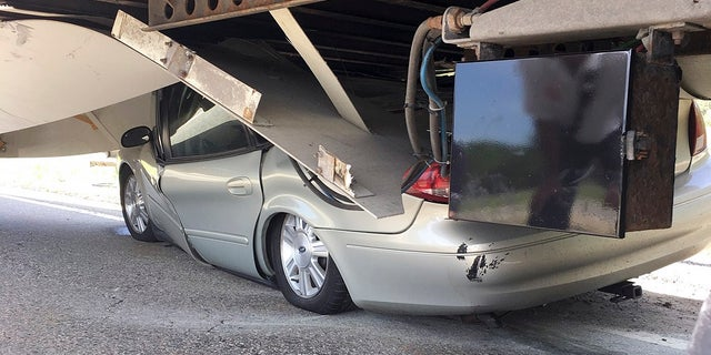 In this Tuesday, July 16, 2019 photo photo released by the Uxbridge Fire Department on its Facebook page, a car sits wedged under a tractor-trailer on Route 146 in Uxbridge, Mass. The motorist<br>