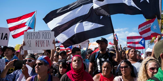 Protesters march in San Juan on Wednesday (AP photo / Dennis M. Rivera Pichardo)