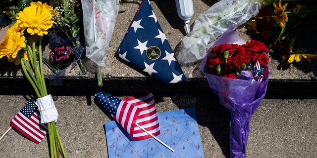 Flags, flowers and letters alike lie near the remains of Wayne Wilson at the conclusion of the memorial service at the Silverbrook Cemetery in Niles, Mich., Wednesday, July 17, 2019. (Emil Lippe/Kalamazoo Gazette via AP)