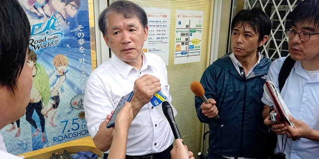 Hideaki Hatta, center, president of Kyoto Animation speaks to the media at the company's headquarters, following a fire of his company's building, in Uji, Kyoto prefecture, western Japan, Thursday, July 18, 2019. (Kyodo News via AP)