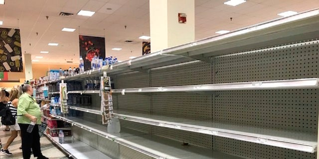 Shoppers look at empty shelfs as a high demand for large jugs of water are sold out at the Coral Ridge Mall Publix after a water main break Thursday, July 18, 2019 in Fort Lauderdale, Fla. (Linda Trischitta/South Florida Sun-Sentinel via AP)