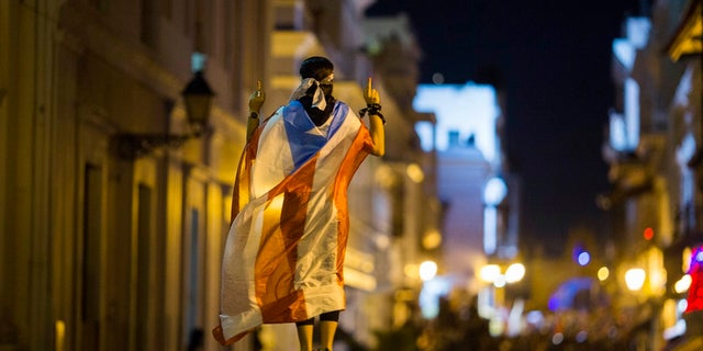 In this Wednesday photo, a demonstrator with a Puerto Rican flag draped over his shoulders balances on the hands of another during clashes in San Juan, Puerto Rico.  (AP Photo/Dennis M. Rivera Pichardo)