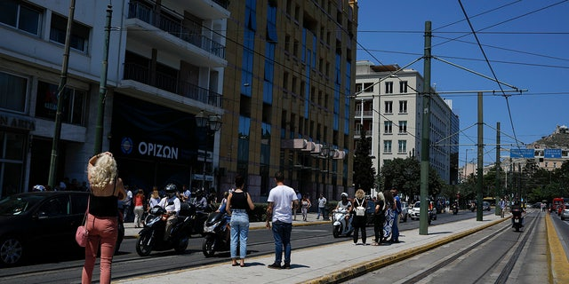 People stand outside the building they work in after a strong earthquake hit near the Greek capital of Athens, Friday, July 19, 2019. The Athens Institute of Geodynamics gave the earthquake a preliminary magnitude of 5.1 but the U.S. Geological Survey gave it a preliminary magnitude of 5.3. The Athens Institute says the quake struck at 2:38 p.m. local time (1113 GMT) about 26 kilometers (13.7 miles) north of Athens. (AP Photo/Petros Giannakouris)