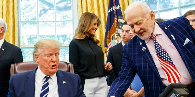 President Donald Trump receives a gift from Apollo 11 astronaut Buzz Aldrin, with first lady Melania Trump, during a photo opportunity commemorating the 50th anniversary of the Apollo 11 moon landing in the Oval Office of the White House, Friday, July 19, 2019, in Washington.