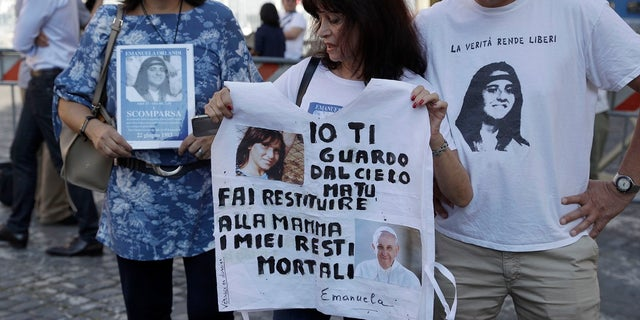 "Reanta Grattani, who claims to be a friend of the Orlandi family, center, holds a t-shirt with the pictures of Emanuela Orlandi and Pope Francis and a writing reading: ""I'm watching you from the sky, but you (referring to Pope Francis) please let them return my mortal remains to my mother"" outside the Vatican, Saturday. (AP Photo/Gregorio Borgia)"