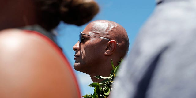 "Actor Dwayne ""The Rock"" Johnson stands during a prayer during a visit to the protests against the TMT telescope, Wednesday, July 24, 2019, at the base of Mauna Kea on Hawaii Island. (Jamm Aquino/Honolulu Star-Advertiser via AP)"