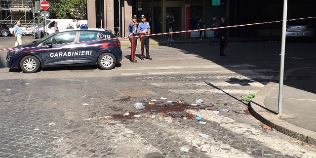 Two Italian Carabinieri, paramilitary policemen, stand near a blood stain, the site where their colleague, Carabiniere Vice Brigadier Mario Cerciello Rega was stabbed to death by a thief in Rome, Friday, July 26, 2019.