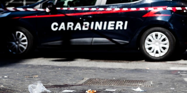 A car of the Italian Carabinieri paramilitary police is parked near a blood stain the site where Carabiniere Vice Brigadier Mario Cerciello Rega was stabbed to death by a thief in Rome on Friday