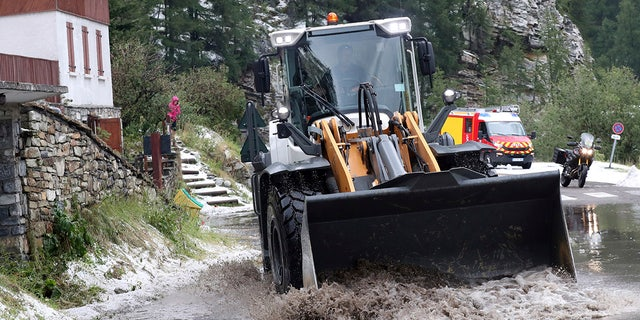 A worker uses a digger to clean the road of the nineteenth stage of the Tour de France cycling race over 126,5 kilometers (78,60 miles) with start in Saint Jean De Maurienne and finish in Tignes, France, Friday, July 26, 2019. Tour de France organizers stopped Stage 19 of the race because of a hail storm as Julien Alaphilippe lost his yellow jersey to Egan Bernal. (AP Photo/Thibault Camus)
