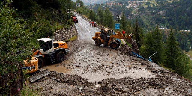 Worker use diggers to clean the road of the nineteenth stage of the Tour de France cycling race over 78,60 miles with start in Saint Jean De Maurienne and finish in Tignes, France.