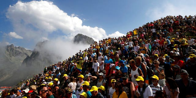 Spectators stand on the Tourmalet pass next to the finish line of the fourteenth stage of the Tour de France cycling race over 73 miles with a start in Tarbes and finish at the Tourmalet pass.