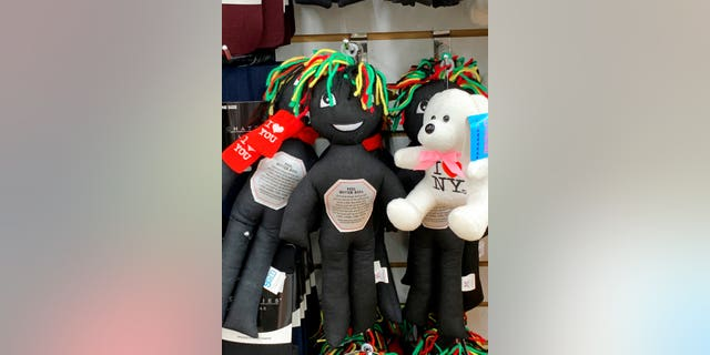 """This undated photo provided by New Jersey state Assemblywoman Angela McKnight shows three """"Feel Better Dolls"""" sharing the shelf with a stuffed animal bearing an """"I Love New York"""" message at a One Dollar Zone store in Bayonne, N.J. The black rag """"Feel Better"""" dolls that came with instructions to """"find a wall"""" and slam the toy against it have been pulled from three stores after customers and the lawmaker said they were offensive. (Angela McKnight via AP)"""