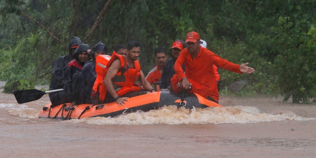 Members of the National Disaster Response Force (NDRF) work to rescue passengers of a stranded train in Badlapur, India Saturday, July 27, 2019. Rescuers in India on Saturday safely evacuated all 700 passengers from a train after it got stuck in monsoon floodwaters between two stations near Mumbai, the country's home minister said. A statement by India's disaster management office in Maharashtra state said the Mahalaxmi Express train got stuck due to flooding of the tracks. (AP Photo/Rafiq Maqbool)