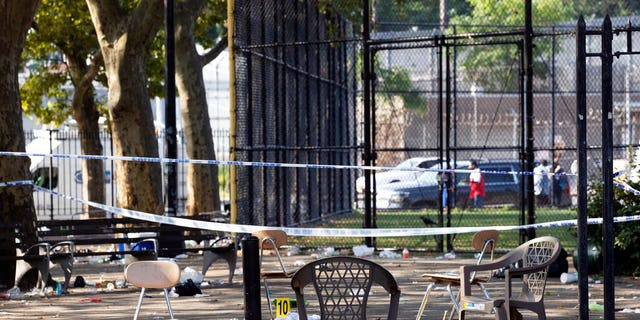 Yellow evidence markers are placed next to chairs at a playground in the Brownsville neighborhood in the Brooklyn borough of New York on Sunday.