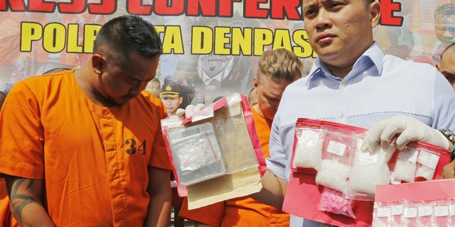 Police officers show evidence as they parade Australian nationals David van Iersel, rear right, and William Cabantog, left, during a press conference at the regional police headquarters in Denpasar, Bali, Indonesia Tuesday, July 23, 2019. Indonesian police say two Australian men have been arrested with cocaine on Bali. (AP Photo/Firdia Lisnawati)