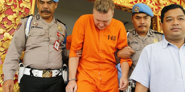 Police officers escort Australian national David van Iersel, center, to a press conference at the regional police headquarters in Denpasar, Bali, Indonesia Tuesday, July 23, 2019. Indonesian police say two Australian men have been arrested with cocaine on Bali. (AP Photo/Firdia Lisnawati)