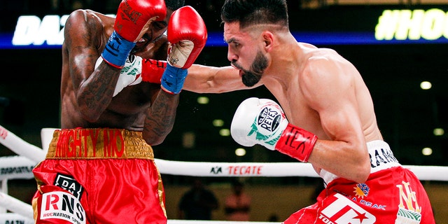 Jose Ramirez, right, lands a punch on Maurice Hooker in the second round of a boxing match, Saturday, July 27, 2019, in Arlington, Texas. Ramirez won in the sixth round with a TKO. (AP Photo/Brandon Wade)
